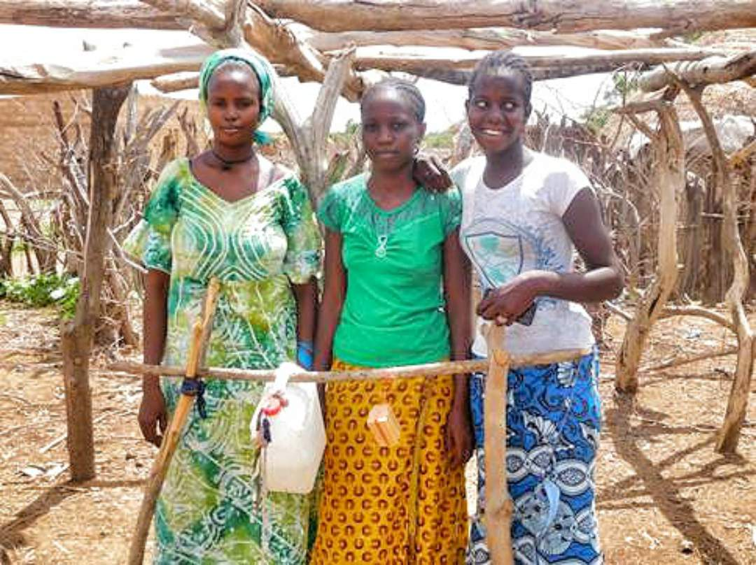 A picture of a local family consisting of 2 students with their hand made hand washing station