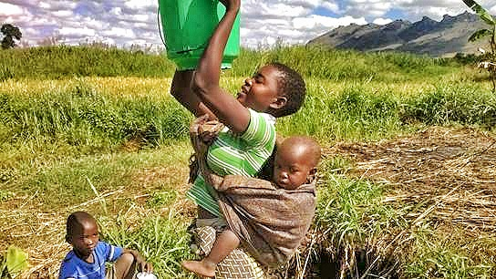 Mama and youth carrying water
